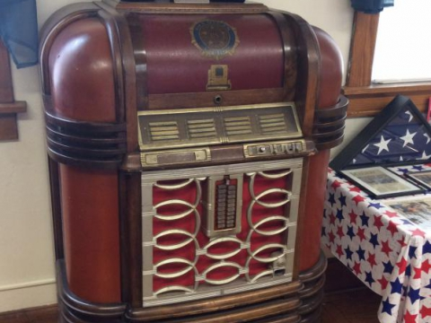 Antique juke box with 75th anniversary whiskey bottles